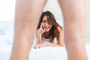 Woman laughing lying in bed looking at men's genital