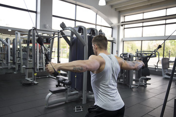 Young Man Using Fitness Equipment In Gym