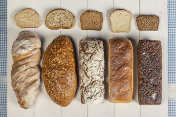 Kromki i bochenki chleba jasnego i ciemnego na drewnianych białych deskach
