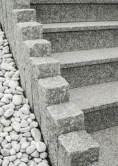 Closeup einer modernen Außentreppe aus Granit mit Stelen und Drainage aus großen weißen Kieselsteinen Closeup of a modern exterior granite staircase with palisades and drainage of large white pebbles