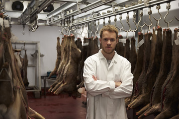 Portrait Of Butcher Standing In Cold Store With Game