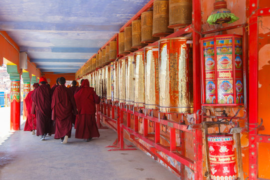 Buddhist nun walking touch a prayer wheels around the sanctuary at Larung gar (Buddhist Academy) in Sichuan, China