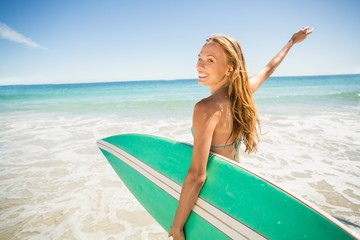 Woman posing with surfboard on beach