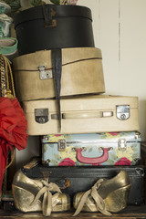 A Stack of Vintage Suitcases and a Pair of Golden Shoes