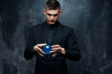 Magician young man in a black suit holds a magical sphere