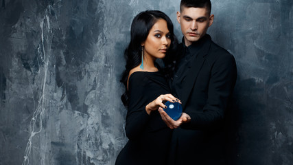 Magician young man and his assistant woman in a black clothes hold a magical sphere