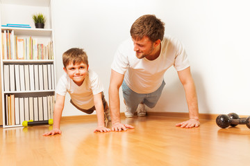 Father teaching kid son doing push-ups exercises