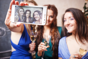 Group of beautiful young women with glasses of champagne making photo on smartphone