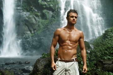 Water. Healthy Man Relaxing Near Beautiful Paradise Green Waterfall. Handsome Fitness Model With Sexy Fit Body, Wet Skin Enjoying Nature Beauty On Summer Travel Vacation. Health Care, Sport Concept