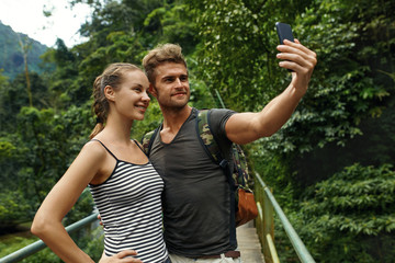 Take Photos. Couple Of Tourist People Making Selfie Photo With Mobile Phone On Summer Vacation. Beautiful Happy Friends, Man And Woman Enjoying Nature Of Tropical Forest. Travel, Tourism, Technology
