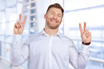 Portrait of a young man smiling with victory sign