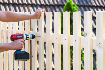 building a wooden fence with a drill and screw. Close up of his