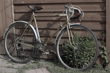 Old vintage bike. Retro road bicycle standing at the wooden wall