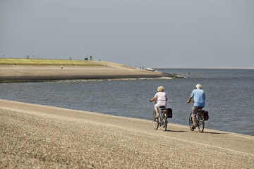 Tender elderly couple on bicycles in the Netherlands