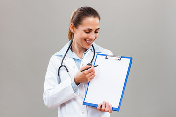 Beautiful female doctor is holding clipboard and showing document with pen.