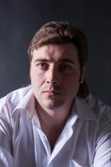 man posing in white shirt on dark background