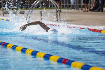 Nadador nadando crol en piscina de verano. Competición de natación. Estilo olímpico. Nadadora compitiendo a estilo libre.