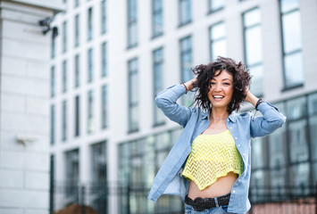 Happy young curly-headed mulatto woman smiling on the background
