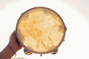 музыкальный инструмент бубен или пандейру на фоне неба в закате