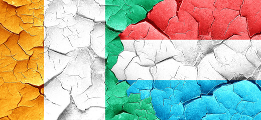 Ivory coast flag with Luxembourg flag on a grunge cracked wall