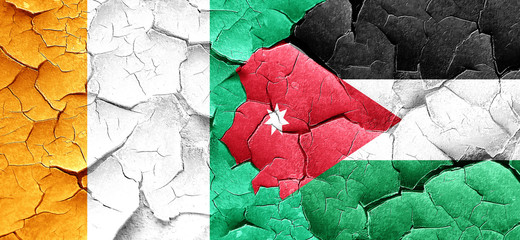 Ivory coast flag with Jordan flag on a grunge cracked wall