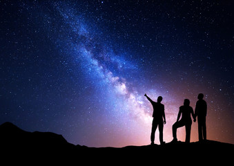Colorful Milky Way with silhouette of a standing man pointing finger in night starry sky and his parents. Silhouette of a family. Night landscape. Beautiful Universe, space background