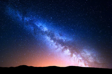 Wall Mural - Night landscape with colorful Milky Way and yellow light at mountains. Starry sky with hills at summer. Beautiful Universe. Space background