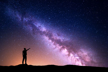 Milky Way with silhouette of a standing man pointing finger in night starry sky on the hill. Colorful night landscape. Beautiful Universe, travel background with purple sky yellow light. Space