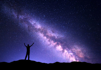 Night colorful landscape with purple Milky Way and silhouette of a standing sporty man with raised up arms on the mountain. Sky full of stars, space.