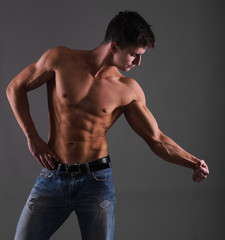 Shirtless muscular guy from back in blue jeans