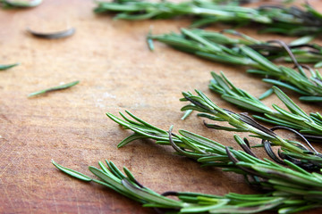 Rosemary bunch on a rustic wooden board. horizontal background