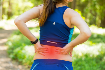 Back pain. Young woman in blue sportswear with smartwatches rubb