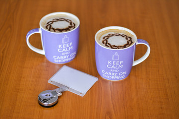 Two big cups of cappuccino, white milk coffee in the morning: keep calm and carry on shopping concept