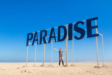 Tourist spreading arms under the Paradise sign.