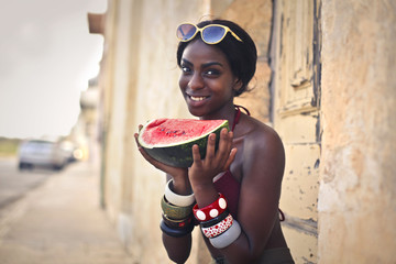 Smiling woman holding a slice of watermelon