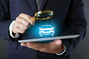 Businessman holding magnifying glass and digital tablet with virtual car on dark grey background