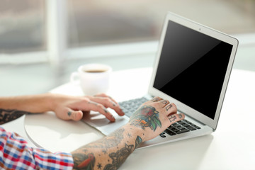 Young man with tattoo using laptop at the table at home