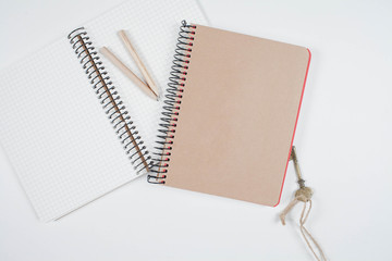 Old notebooks and pencils, key on white table