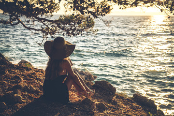 A girl in a hat sitting by the sea.