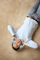 Handsome man with headphones lying on floor