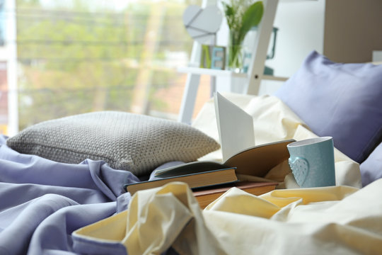 Unmade bed with crumpled blue bed linens and books