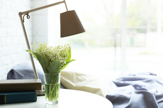 Lamp, books and flower bouquet on a side table