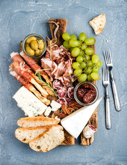 Cheese and meat appetizer selection. Prosciutto di Parma, salami, bread sticks, baguette slices, olives, sun-dried tomatoes, grapes nuts on rustic wooden board