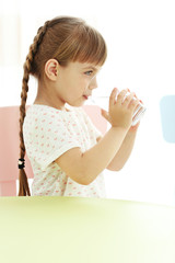 Cute little girl drinking water at table