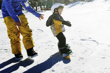 High angle view of father assisting daughter in snowboarding