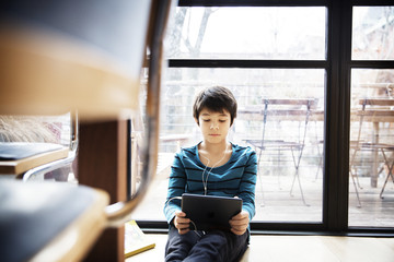 Boy using digital tablet while sitting by window at home
