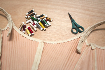 Fabric with colorful spools and scissors on table at workshop