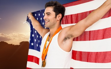 Athlete posing with gold medals and american flag after victory against image of landscape
