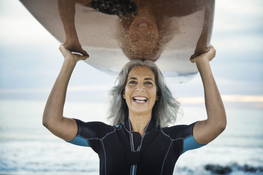 Portrait of smiling woman carrying surfboard at beach