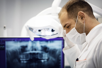 Male dentist adjusting lamp against x-ray in clinic